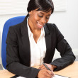 Beautiful black business woman signing document — Stock Photo #6165438