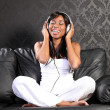 Smiling black woman on sofa listening to music — Stock Photo