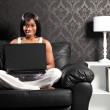 Happy smiling black woman on sofa surfing internet — Stock Photo #6166746