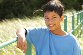 Boy on fence rail in countryside — Stock Photo
