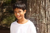 Close up young boy big smile leaning against tree — ストック写真