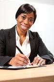 Mujer de negocios negro feliz firma de documento — Foto de Stock