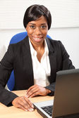 Happy beautiful black woman using laptop in office — Stock Photo