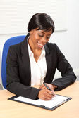 Beautiful black business woman signing document — Stock Photo