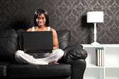 Happy smiling black woman on sofa surfing internet — Stock Photo