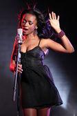 Bela cantora negra no palco com microfone — Fotografia Stock