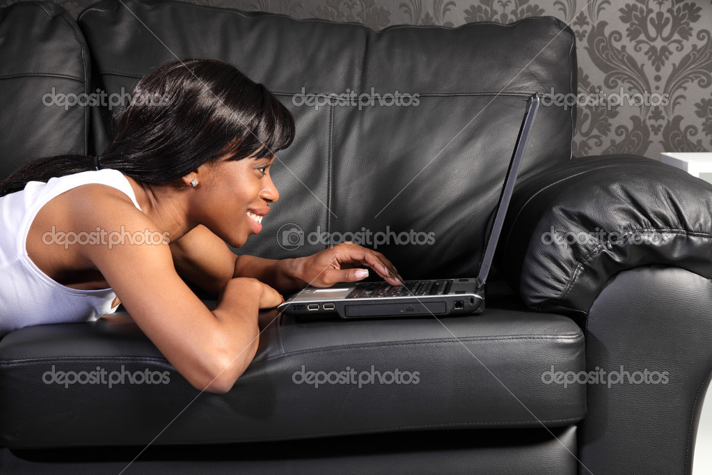 Beautiful smiling young african american woman lying on black leather sofa at home, surfing facebook on the internet with her laptop computer. — Stock Photo #6166698