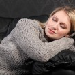 Beautiful blond woman asleep in grey knit sweater - Stock Photo
