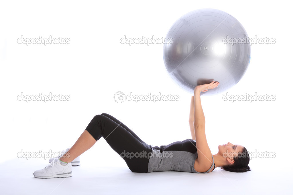 Beautiful athletic young woman lying on her back working triceps brachii muscles with a fitness exercise ball. She is wearing a grey and black sports clothes — Stok fotoğraf #6212497