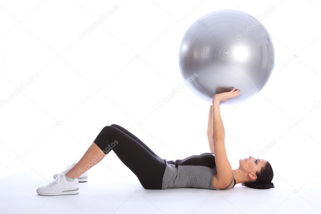 Beautiful athletic young woman lying on her back working triceps brachii muscles with a fitness exercise ball. She is wearing a grey and black sports clothes — Foto Stock #6212497