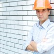 Royalty-Free Stock Photo: Young worker standing near a wall