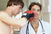 Doctor receiving a punch from a boxer — Stock Photo