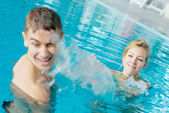 Teenage couple splashing a t the swimming pool — Stock Photo