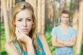 Upset teenage girl and a boy a thte background — Stock Photo