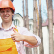 Smiling young worker with a thumb up outdoors — Stock Photo