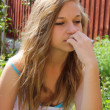 Beautiful teenage girl in garden stressed out — Stock Photo