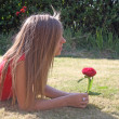 Teenage girl with red flower — Stock Photo