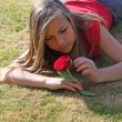 Stock Photo: Teenage girl playing with flower