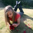 Teenage girl playing with flower — Stock Photo
