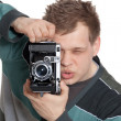 A young man is focused photographing old camera - Stock Photo