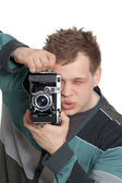 A young man is focused photographing old camera — Стоковое фото