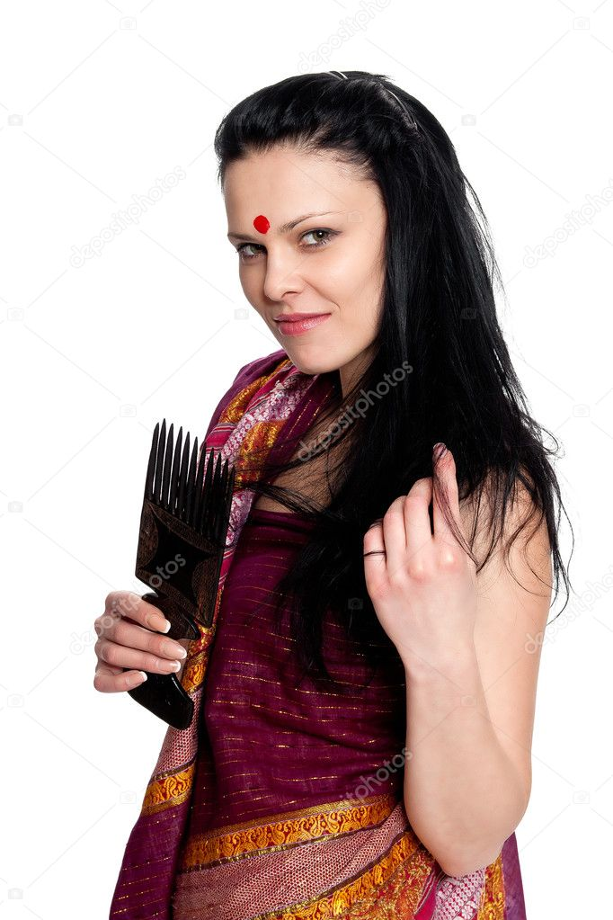 A beautiful brunette in the Indian sari combs comb hair posing in studio on white background — Stock Photo #6347007