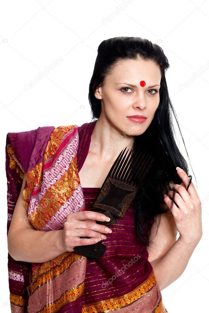 A beautiful brunette in the Indian sari combs comb hair posing in studio on white background — Stock Photo #6347016