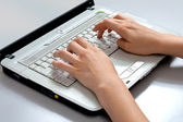 Women's hands close-up on the laptop keyboard — Stock Photo