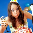 Woman blowing birthday candles - Stock Photo