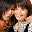 Stock Photo: Cheek to cheek smiling violinists