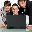 Happy coworkers behind a laptop — Stock Photo