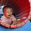 Happy kid in a playground tunnel — Stock Photo
