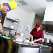 Couple of cooks in a restaurant kitchen - Stock Photo