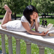 Student reading books in the park — ストック写真