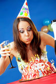 Woman blowing birthday candles — Stock Photo