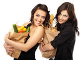Two women holding groceries — Stok fotoğraf