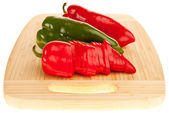 Red and green peppers on a board — Stock Photo