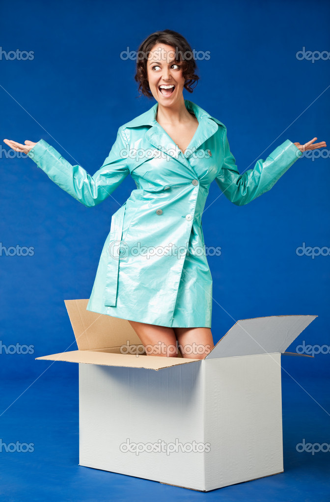 Happy woman dressed in raincoat coming out of the box — Stock Photo #6374066