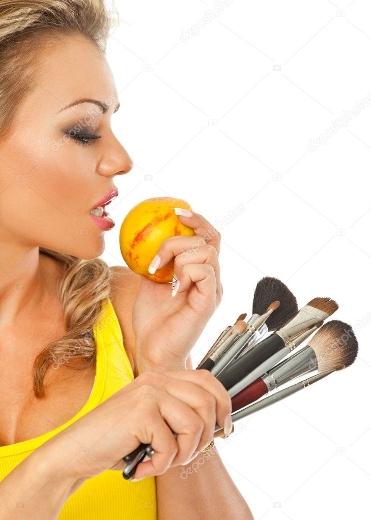 Gorgeous female holding a peach in one hand and makeup brushes in other — Stock Photo #6374777