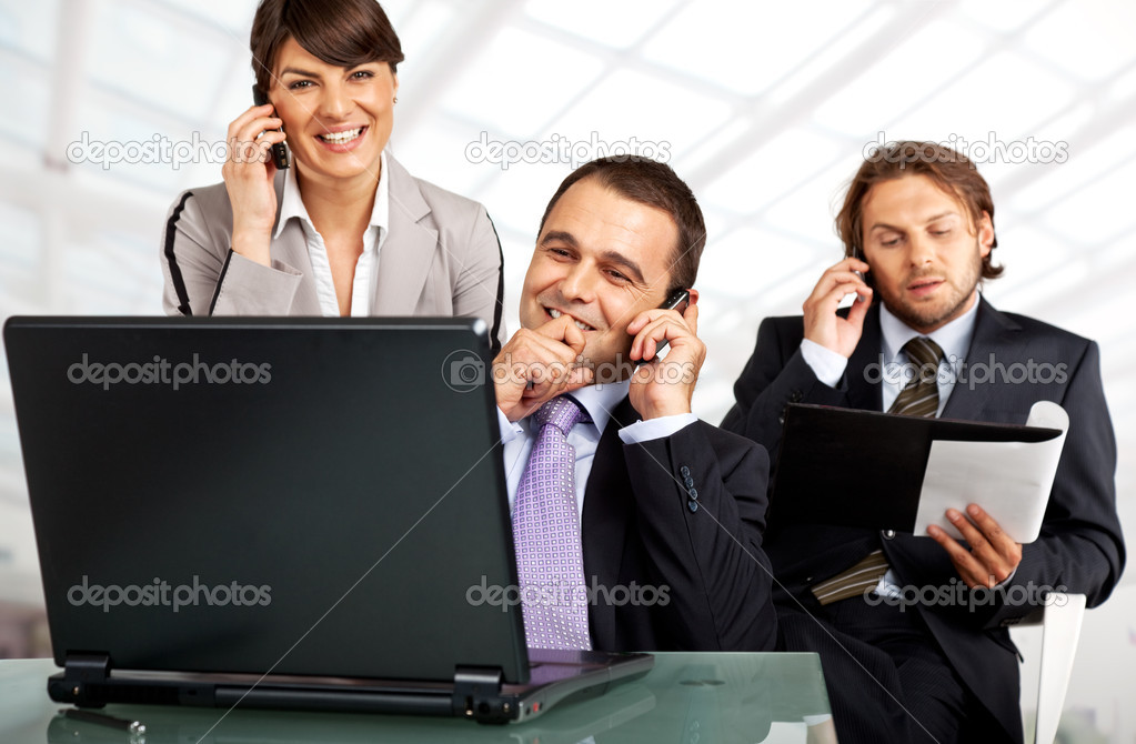 Business team of three on their phones with a laptop — Stock Photo #6374888