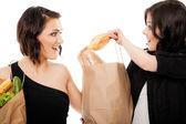 Girlfriends fighting over baguette — Stock Photo