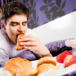 Young male biting croissant bed — Stock Photo