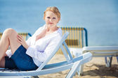 Beautiful woman sitting in chaise — Stock Photo
