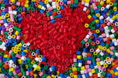 Heart arranged with colorful beads — Stock Photo