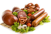 Sausages and ham with lettuce, garlic and tomatoes — Stock Photo