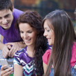 Group of friends reading message on a mobile phone — Stock Photo