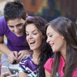 Group of friends reading message on a mobile phone — Stock Photo #6441763
