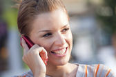 Girl talking on the phone and smiling — Stock Photo