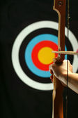 Young man holding bow and shooting to target — Stock Photo
