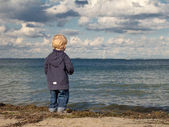 Little boy at a beach looking towards the sea in autumn — Stock Photo